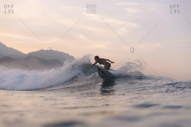 Indonesia- Sumatra- female surfer in the evening light