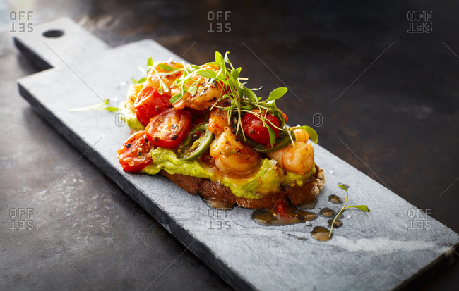 Crostini with shrimps and tomatoes- roasted bread- herbs- avocado cream- sweet chili sauce- jalapenos- cress