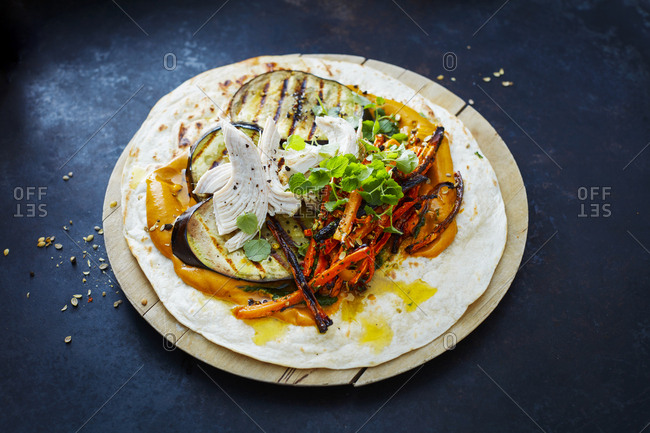 Pulled Chicken Wrap- carrot- grilled aubergine- curry hummus and herbs on chopping board