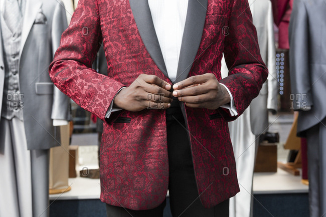 Mid section of a man dressing tuxedo in tailor shop