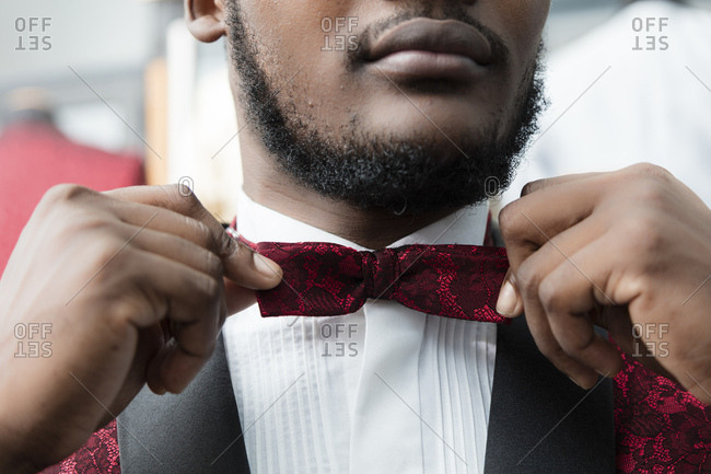Close-up of a man wearing tuxedo in tailor shop adjusting the bow tie