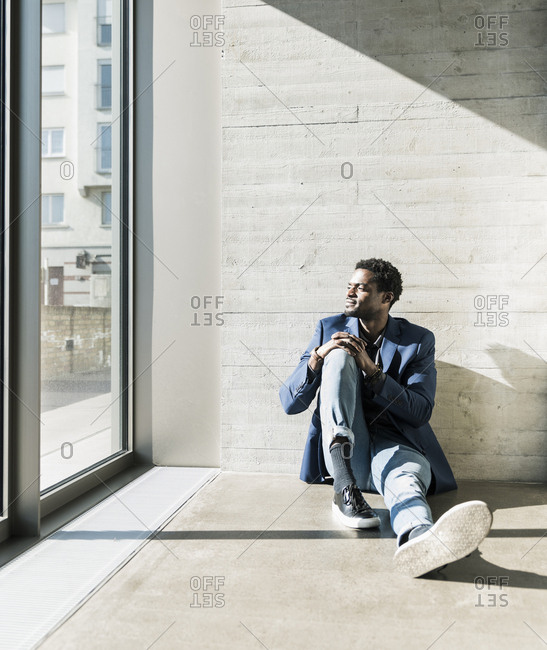 Businessman sitting on the floor in sunshine looking out of window