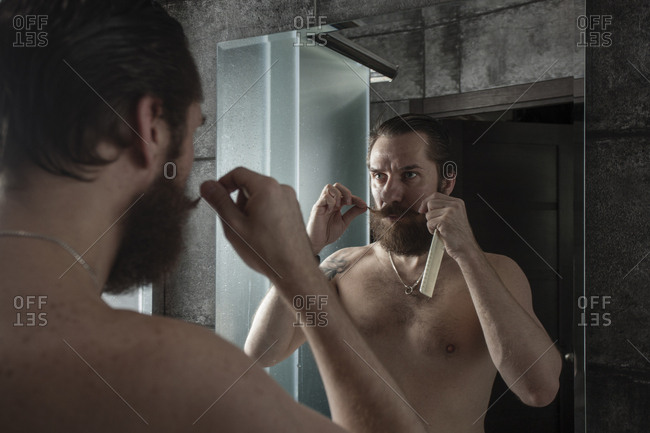 Portrait of bearded man looking at his mirror image while twirling his beard