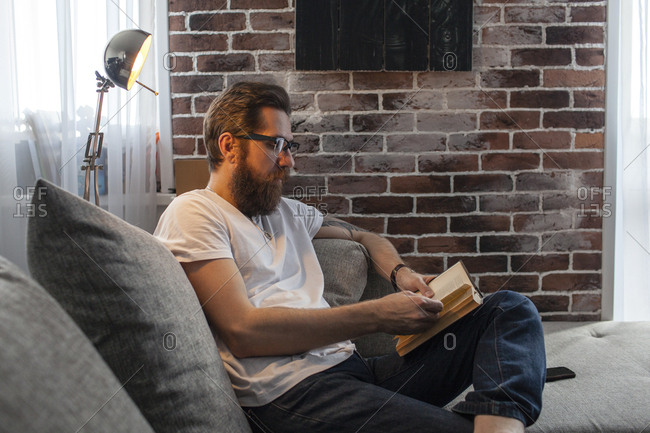 Man sitting on couch at home reading a book