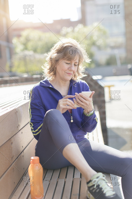 Active senior woman using mobile phone after workout in city on sunny day