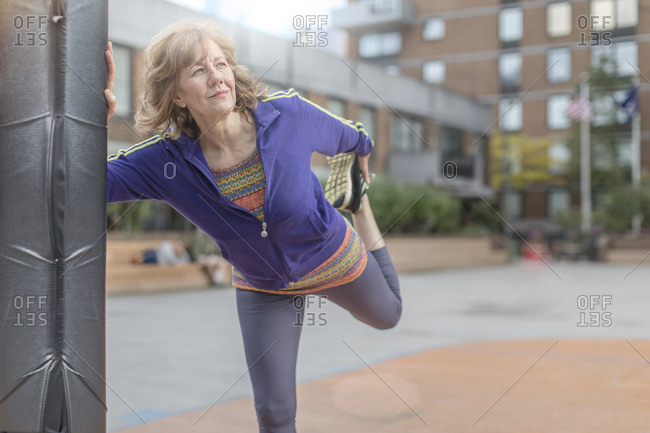 Active senior woman doing stretching exercise in city