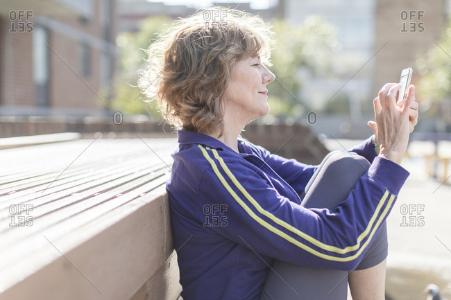 Side view of fit senior woman using cell phone after workout in city