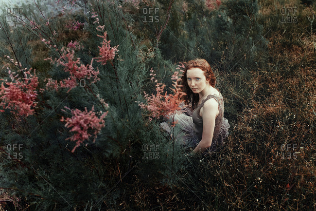 Redhead freckled teenage girl in the grass