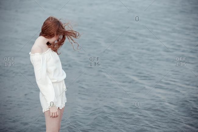 Redhead teenage girl standing at the sea