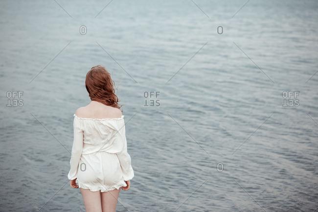 Redhead teenage girl looking at the sea