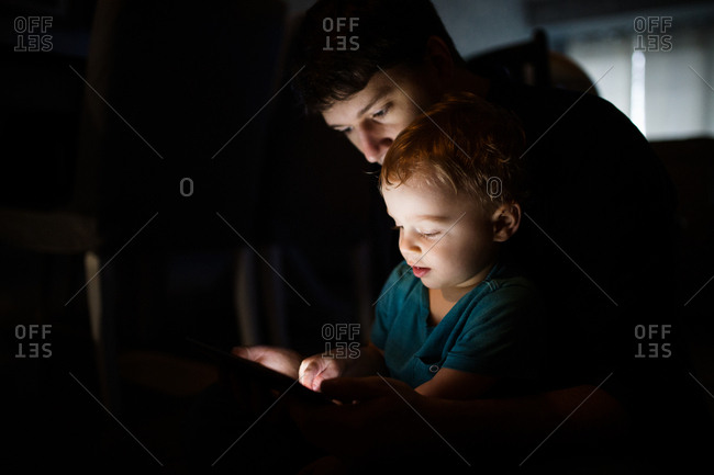 Father and son looking at tablet in dimly lit room