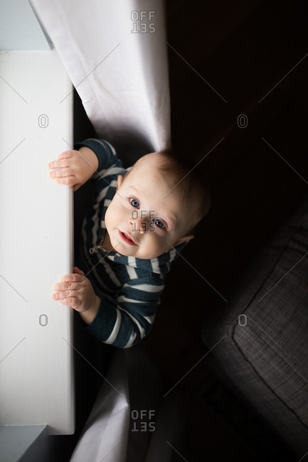 Overhead view of baby holding onto window ledge looking up