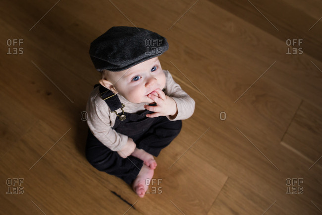 5fac0cbd Baby boy wearing overalls and ivy cap stock photo - OFFSET
