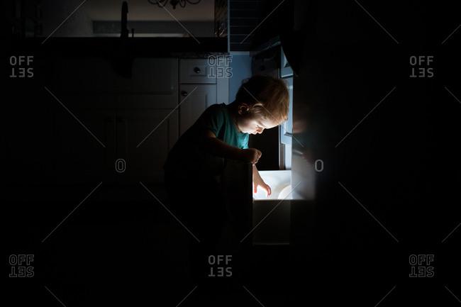 Little boy reaching into lit kitchen drawer
