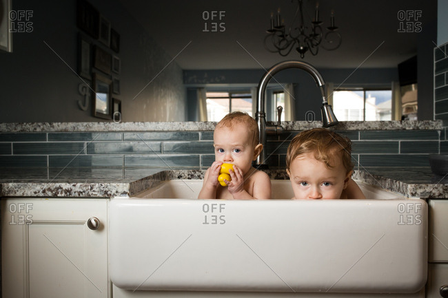 Two boys bathing in kitchen sink together