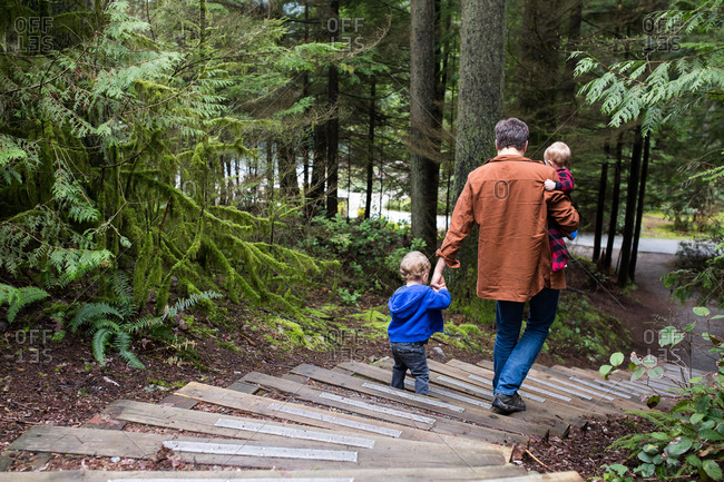 Father walking on steps in the forest with two small sons