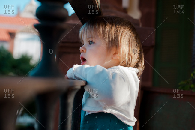 Baby girl amazed by what she is seeing from her balcony