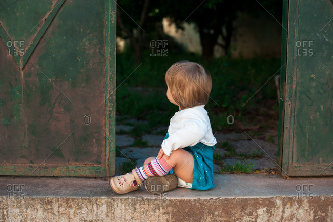Rearview of toddler sitting outside gate to backyard looking in