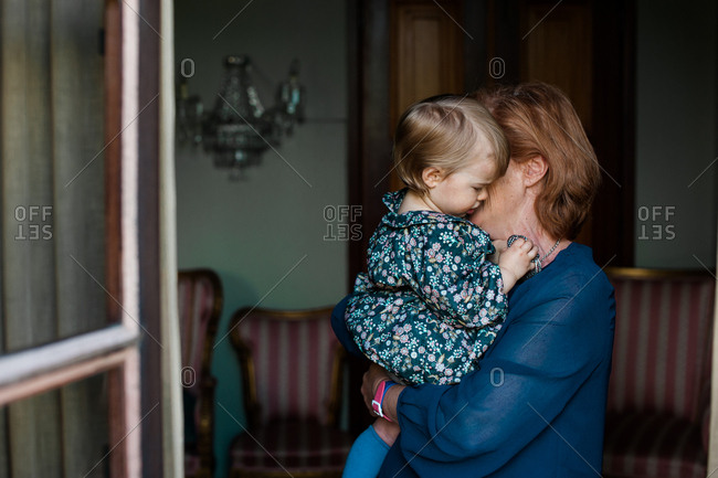 Grandmother carrying and cuddling little granddaughter as seen through open window