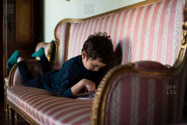 Young boy lying on belly on couch surfing internet on tablet computer