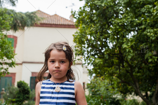 Young girl in stripy dress standing in garden looking annoyed