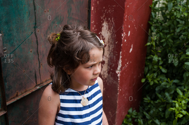 Young girl standing by garden gate looking worried