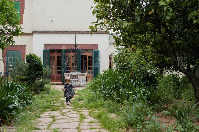 Little girl taking a walk along garden path all by herself