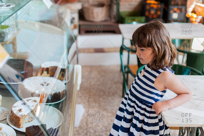 Young girl standing by display case eyeing cakes in bakery