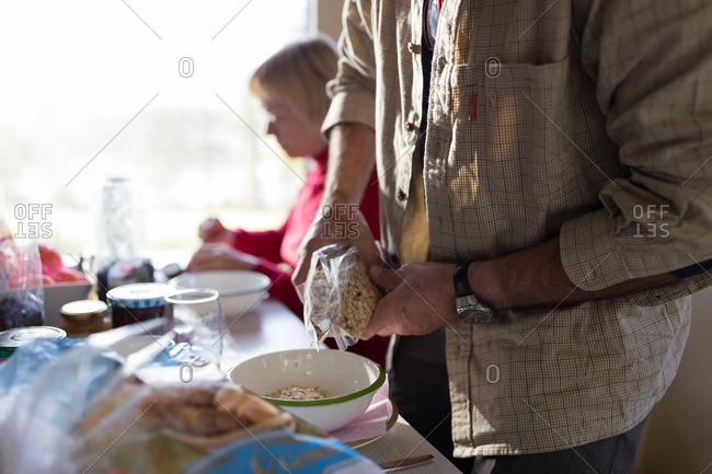 Senior man pouring breakfast cereals