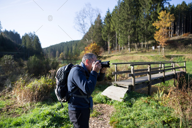 Mature man photographing nature in forest