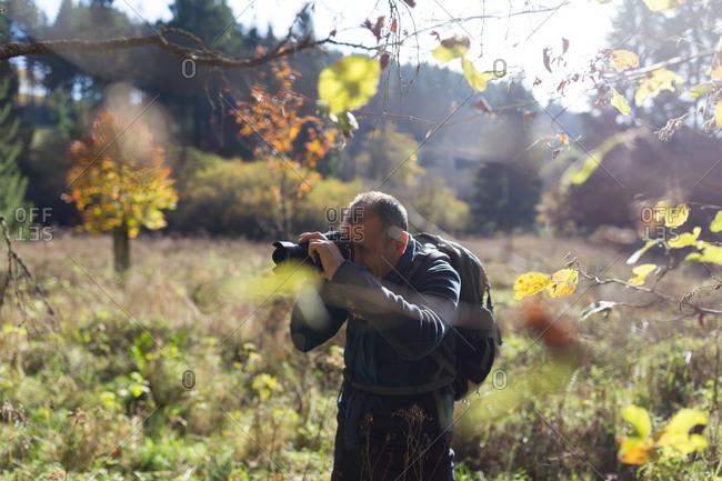 Mature man taking pictures of the forest in fall