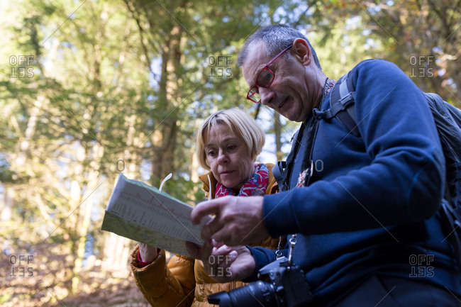 Senior couple looking at map in the woods during fall