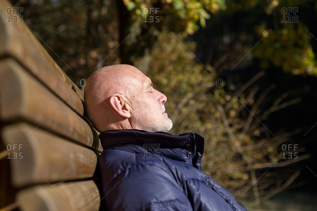 Senior man sunbathing on bench in nature