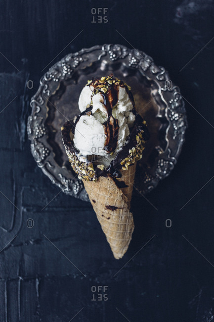 Chocolate coated ice cream cone with vanilla ice cream topped with chocolate syrup and chopped nuts