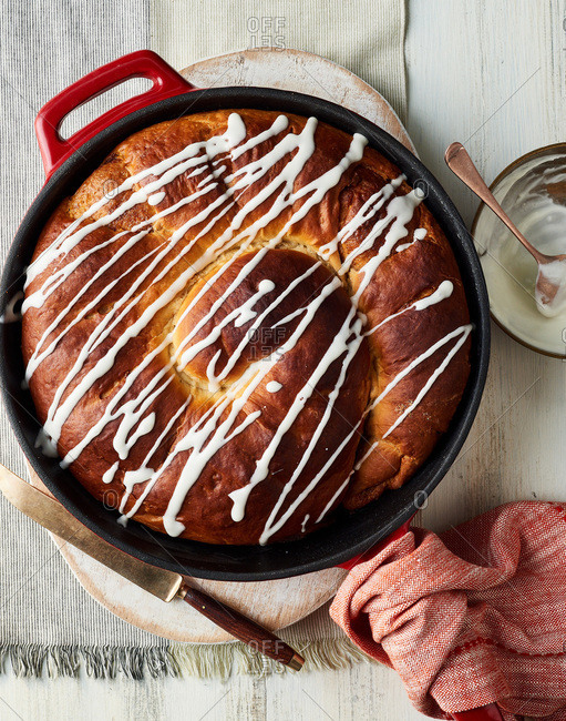 Freshly baked big cinnamon roll in a cast iron skillet drizzled with icing