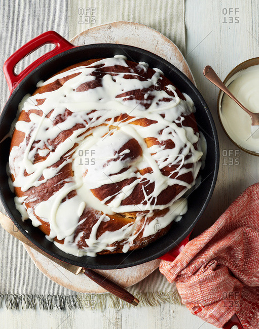 Freshly baked big cinnamon roll in a cast iron skillet topped with icing