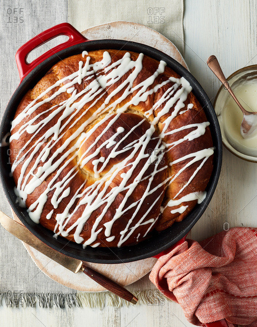 Big homemade cinnamon roll in a cast iron skillet drizzled with icing