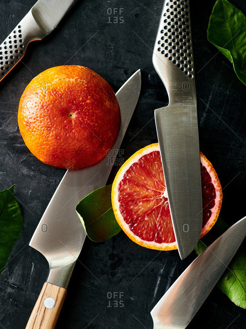 Kitchen knives and a sliced blood orange