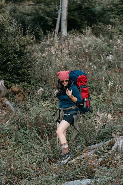 A woman hiking alone in the woods. A female tourist walking through rough terrain.