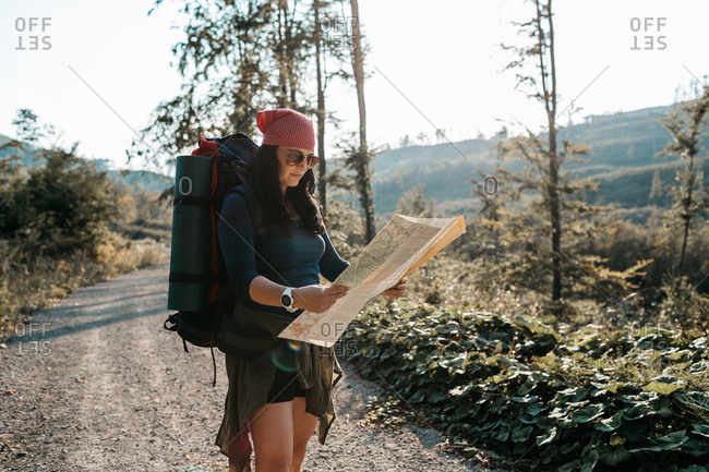 A female hiker reading a map. A portrait of a woman with a backpack checking a map.