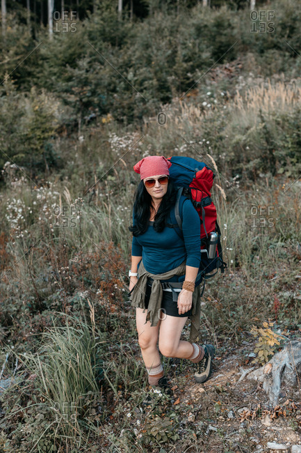 A woman backpacking alone in the wilderness. A portrait of a female hiker hiking in the woods on her own.