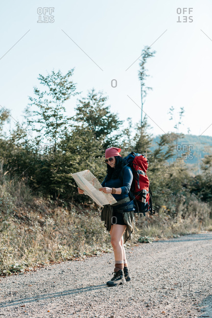 A female hiker with a backpack reading a map. Looking for directions - a woman with a rucksack checking a map.