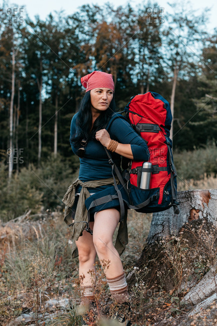 A female hiker putting on a rucksack. A portrait of a woman with a backpack setting off on a trek.