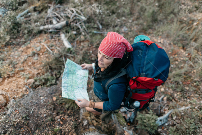 Top view of a woman hiker with a map looking for directions. Solo hiking - a female backpacker hiking alone in the wilderness.