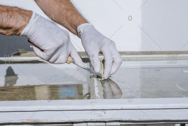 Senior man working in his back yard and repairing wooden windows.