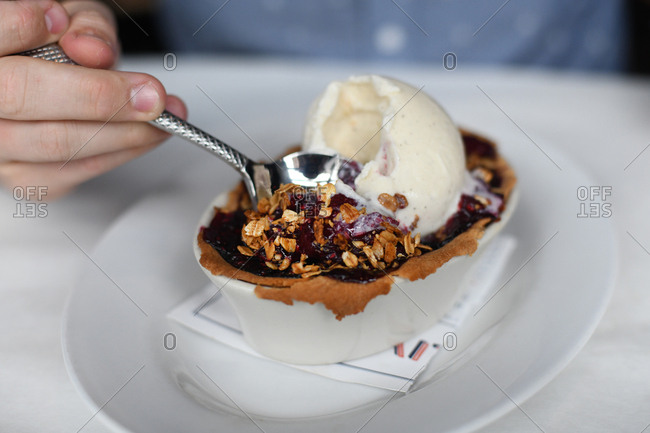 Person eating berry crisp topped with granola and vanilla ice cream