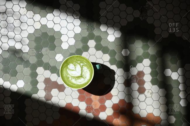 Green tea latte served on tiled surface