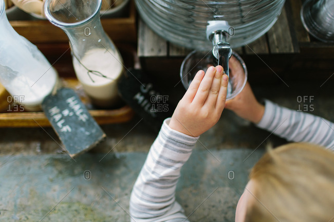 Child filling a cup with water from dispenser