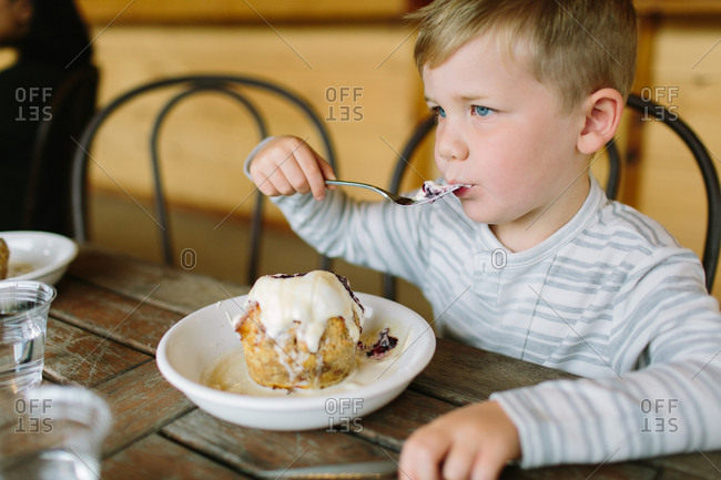 Boy sitting at table eating dessert