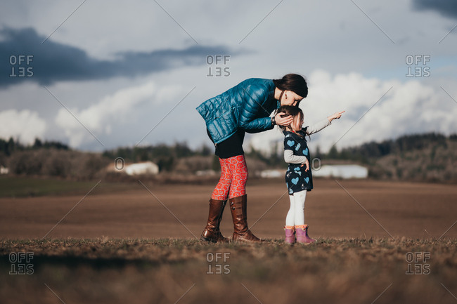 Girl standing in a field and pointing while her mother kisses her head